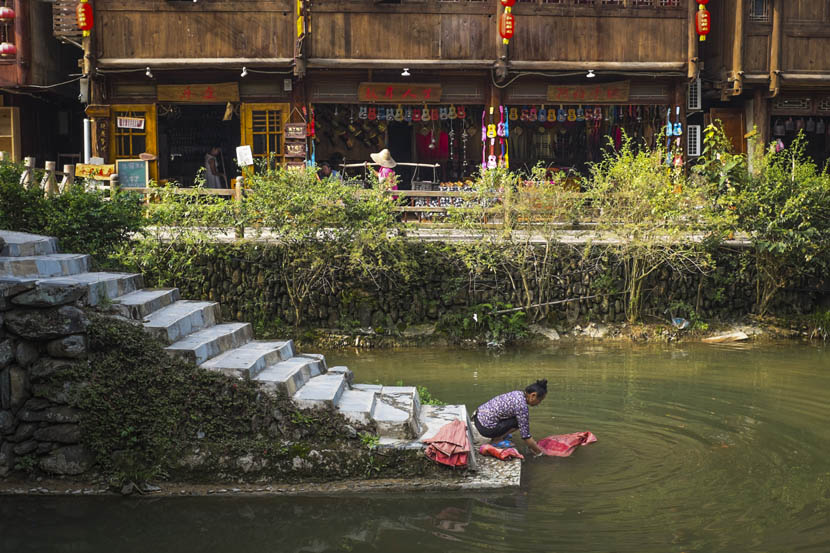 A Dong woman washes clothes in the river, with souvenir shops for tourists in the background, Zhaoxing, Guizhou province, Aug. 24, 2016. Denise Hruby/Sixth Tone