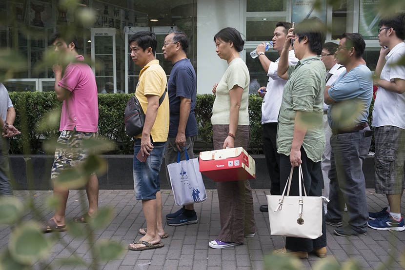 People with coupons wait in line to buy mooncakes outside Xin Hua Lou on Fuzhou Road, Shanghai, Sept. 13, 2016. Xiao Muyi/Sixth Tone