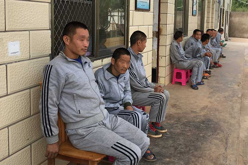Mentally disabled men who are unable to remember their home addresses sit outside a rescue center in Xuanwei City, Yunnan province. Peng Yu/Sixth Tone
