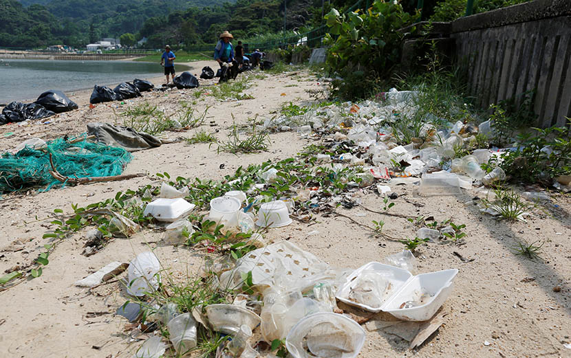 Workers clean Nim Shue Wan beach at Hong Kong's Lantau Island. Environmentalists claim trash is washed ashore from mainland China, July 8, 2016. Bobby Yip/VCG