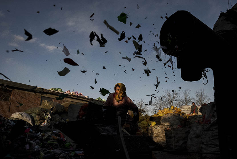 A Chinese laborer in Dong Xiao Kou village, near Beijing, loads a grinding machine with plastics to be recycled, Dec. 15, 2014. Kevin Frayer/Getty Images/VCG
