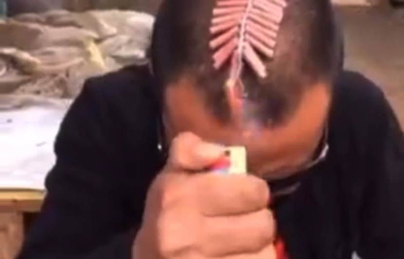 A screenshot from Kuaishou shows a man setting off firecrackers on his head.