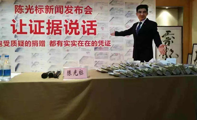 Chen Guangbiao gestures to books on a table during the news conference in Nanjing, Jiangsu province, Sept. 23, 2016. VCG