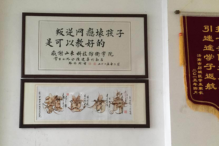 A framed piece of traditional calligraphy hanging in the school reads: 'Rebellious, bad children who are addicted to the internet can be made good again,' at Shandong Science and Technology Defense College in Jinan, Sept. 21, 2016. Owen Churchill/Sixth Tone