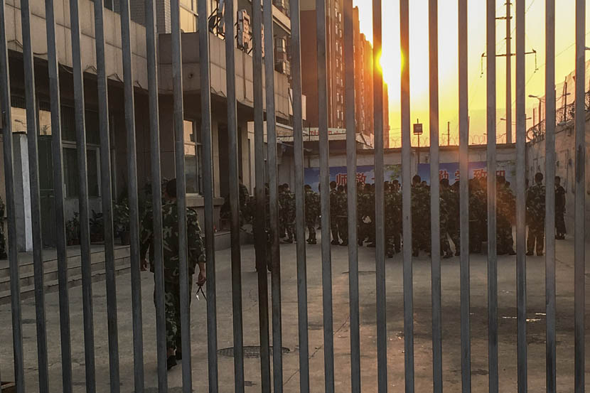 Students in camouflage uniform are seen through bars as they form a line for their evening meal at Shandong Science and Technology Defense College in Jinan, Sept. 21, 2016. Peng Wei/Sixth Tone