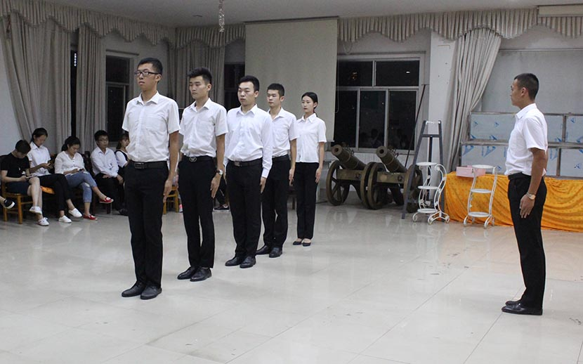 Students practice standing in a way that shows respect at the department of funeral services at Changsha Social Work College, Hunan province, Sept. 20, 2016. Cai Yiwen/Sixth Tone