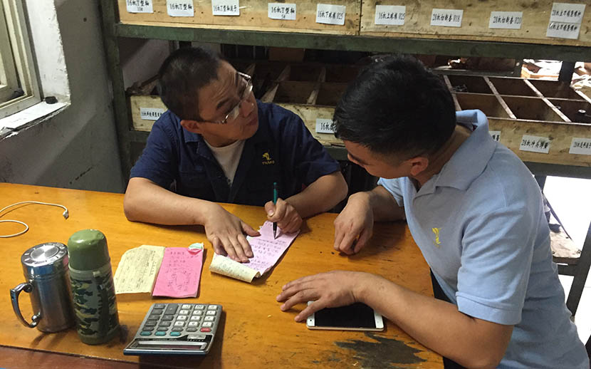 Dong Ming writes notes in order to communicate with his deaf colleague at the factory in Tongling, Anhui province, Sept. 23, 2016. Fu Danni/Sixth Tone