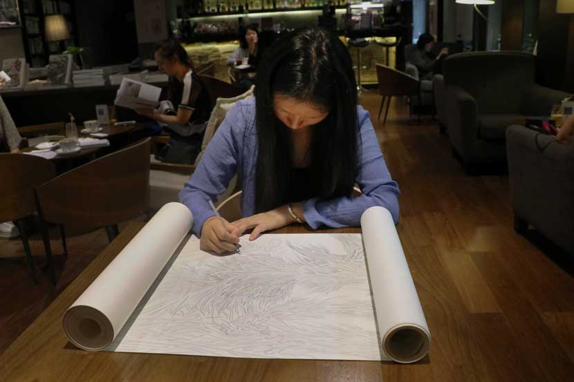 Ji Hongyan draws on a scroll at One Way Space bookshop in Beijing, Sept. 21, 2016. Yin Yijun/Sixth Tone
