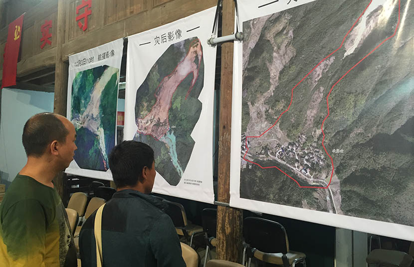 In the wake of a deadly landslide, residents look at 'before' and 'after' satellite images of Su Village, Zhejiang province, Oct. 8, 2016. Fu Danni/Sixth Tone