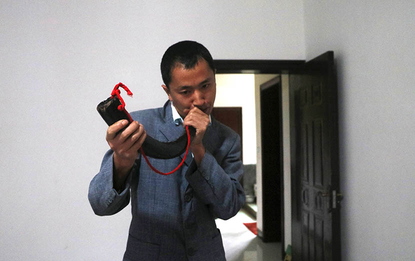 Zhang Gang blows an ox horn at the house where he lives with his father in Shaowo Town, Guizhou province, Sept. 27, 2016. Yin Yijun/Sixth Tone