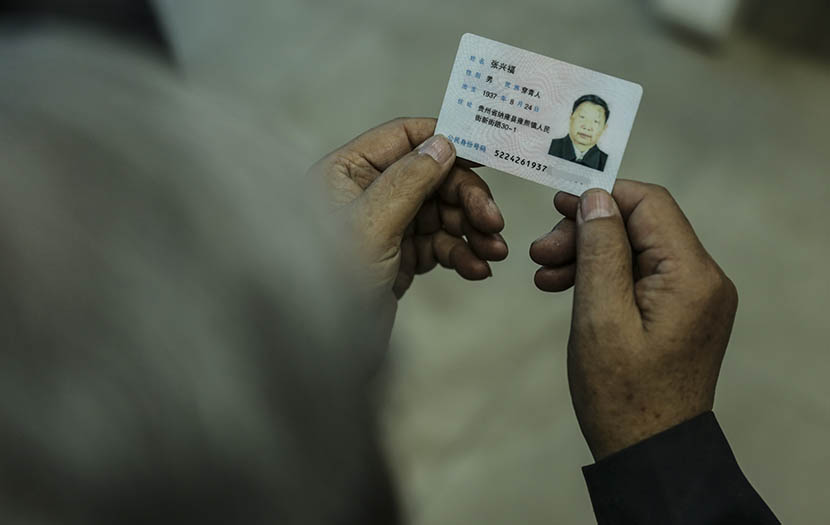 "A man shows his identity card on which his ethnicity reads as ""Chuanqing"" in Shaowo Town, Guizhou province, June 14, 2016. Li Kun/Sixth Tone"