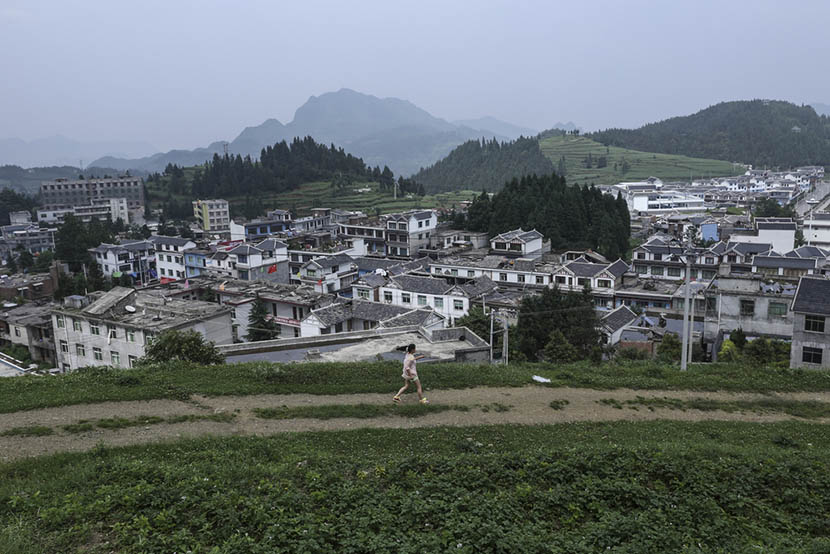 A girl runs along the hillside in Shaowo Town, Guizhou province, June 14, 2016. Li Kun/Sixth Tone