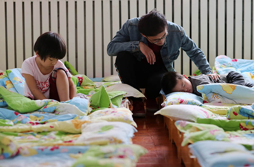 A male teacher wakes up his students after their afternoon nap at a kindergarten in Xingtai, Heibei province, April 25, 2016. Hao Yaxin/VCG