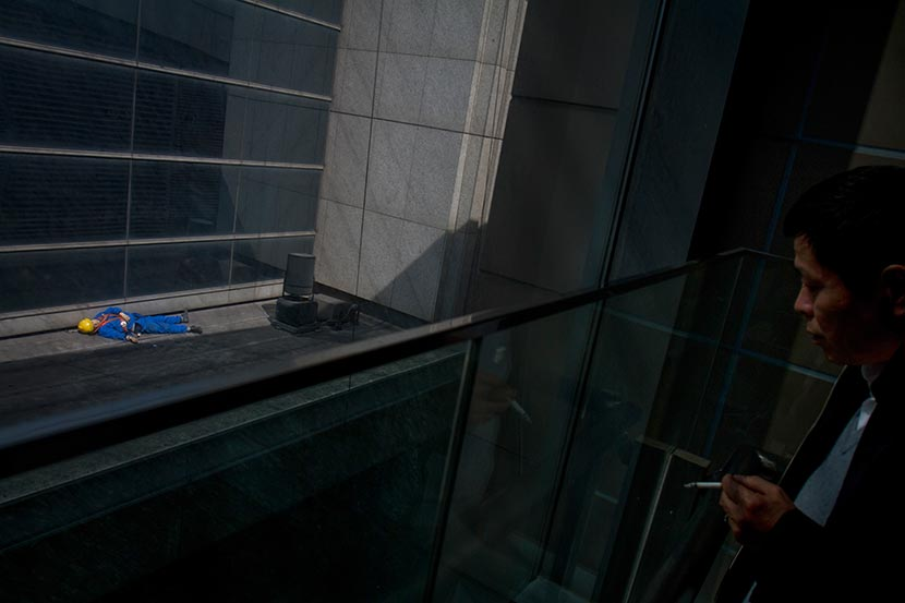 A man standing on a balcony looks at the body of a high-rise window washer who fell to his death in Shanghai's central business district, March 21, 2013. Yang Shenlai/Sixth Tone