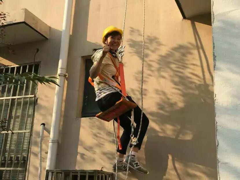 Quan Minmin, one of the few female high-rise window washers in China, poses during safety training in Wuxi, Jiangsu province, 2015. Courtesy of Quan Minmin