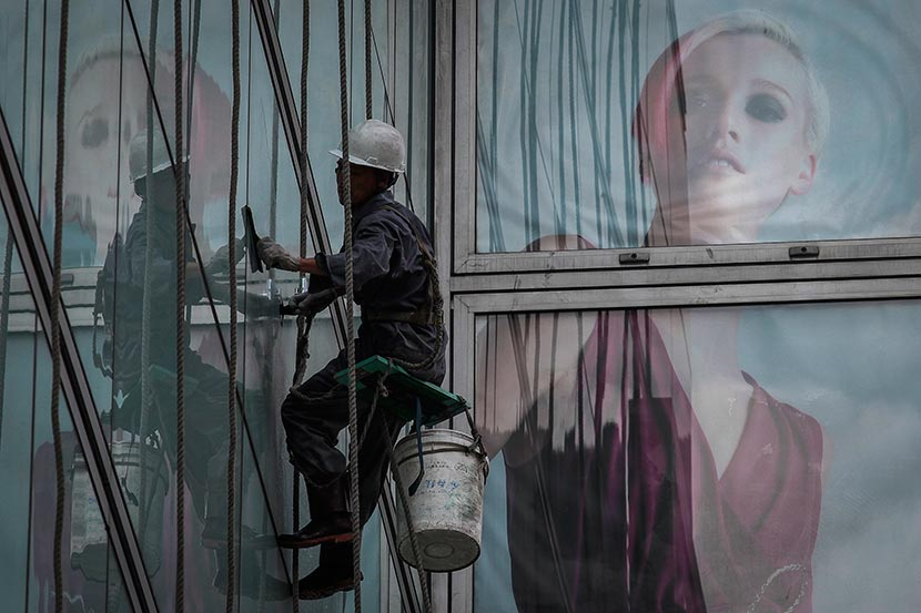 A high-rise window washer at work in downtown Shanghai, Aug. 29, 2012. Gao Zheng/Sixth Tone