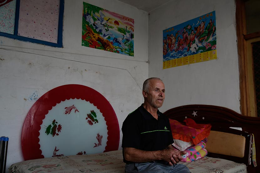 Qiu Changli sits on a bed at his home in Bianjiang Village, Heilongjiang province, Aug. 2, 2016. Han Meng/Sixth Tone