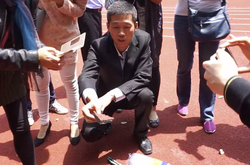 Wei Wenfeng tests handles a sample of running track at a primary school in Kunshan, Jiangsu province, April 2016. Courtesy of Daddy Lab