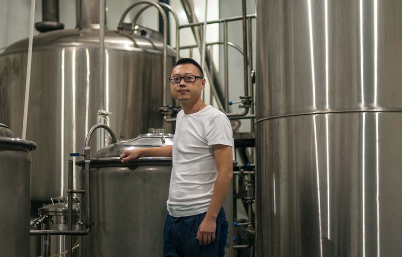 Wang Rui poses with his original 200-liter brewing system, with his new 2,000-liter apparatus in the background, Chengdu, Sichuan province, Oct. 9, 2016. Courtesy of Mark Andrews