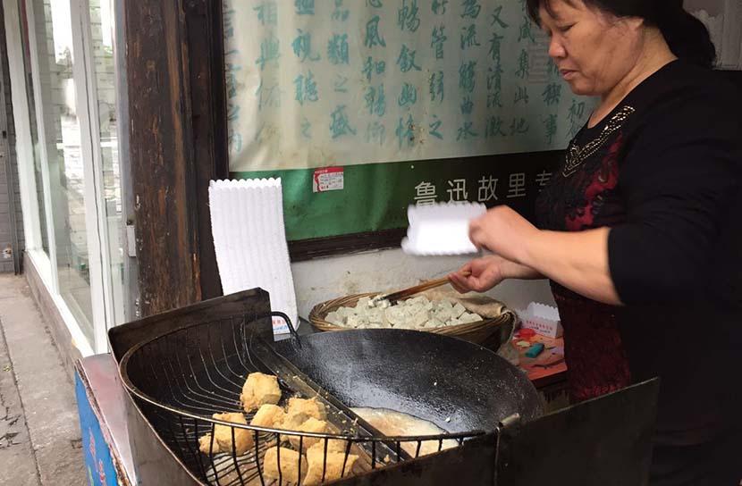 Zhao Baoxian's wife fries stinky tofu at her food store in Shaoxing, Zhejiang province, Oct. 29, 2015. Wang Lianzhang/Sixth Tone