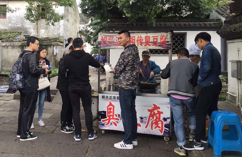 Customers buy stinky tofu from a food stand in Shaoxing, Zhejiang province, Oct. 29, 2015. Wang Lianzhang/Sixth Tone
