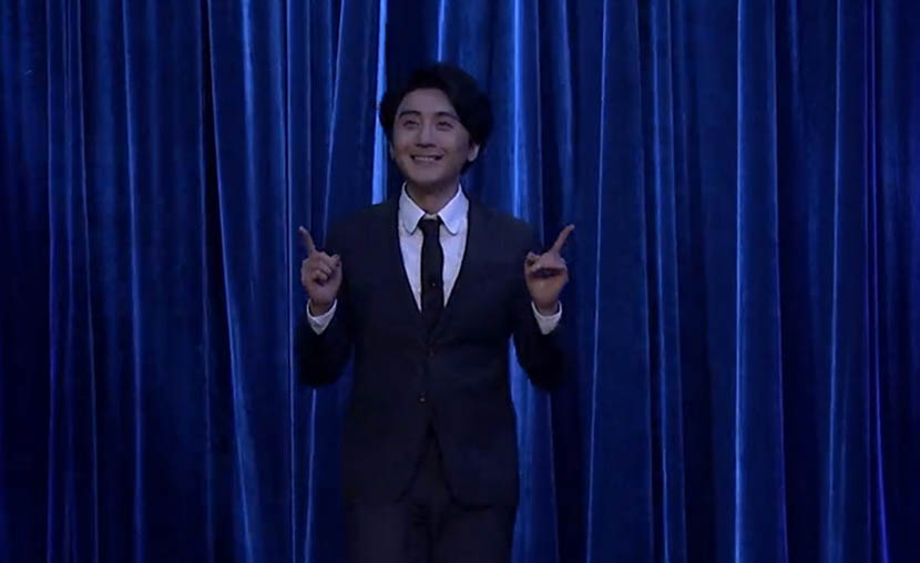 A screenshot from 'The Vicious Liang Huan Show' shows host Liang Huan appearing on stage with a smile.
