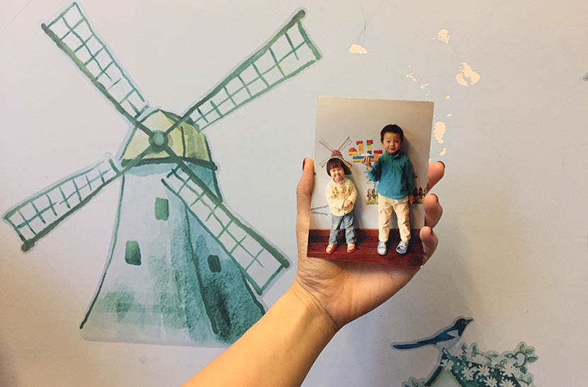 Lai Xiaolan holds up a photo of her children at home in Shanghai, Oct. 29, 2016. Fu Danni/Sixth Tone