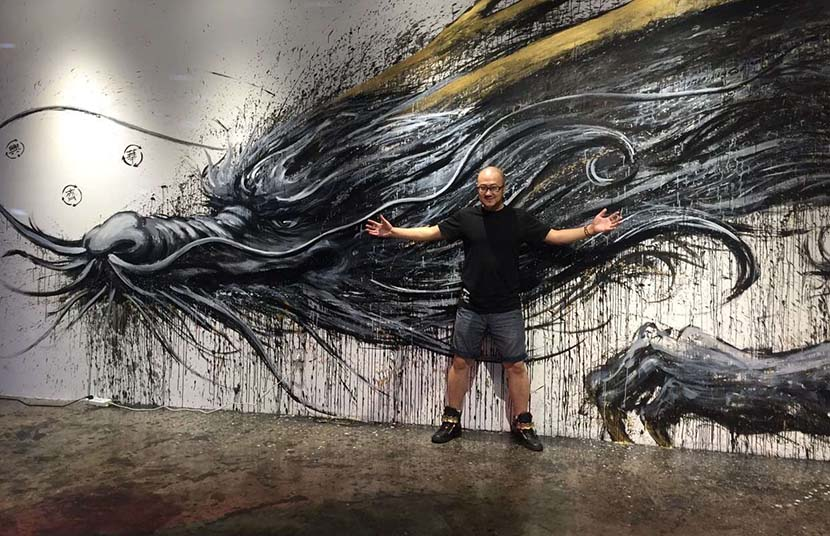 Qi Xinghua poses for a picture in front of his work. Courtesy of Qi Xinghua