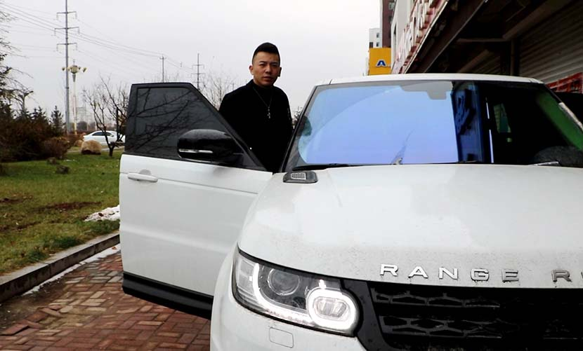 Yu Li stands by his Range Rover in Gongzhuling, Jilin province, Nov. 10, 2016. Yin Yijun/Sixth Tone