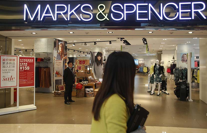 A woman passes by a Marks & Spencer store in Shanghai, March 4, 2015. Gao Zheng/Sixth Tone