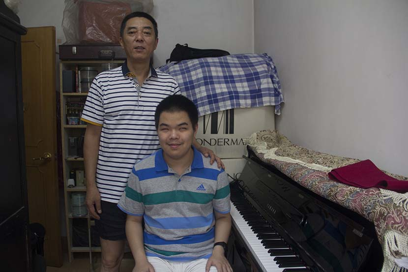 Lai Jiajun and his father pose for a photo in their apartment in Beijing. Wang Chengwei for Sixth Tone