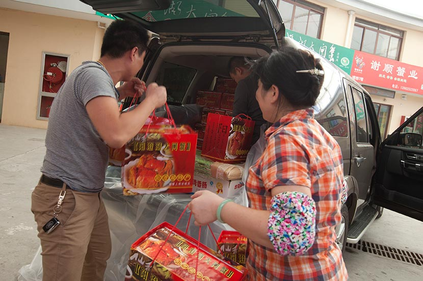 Several people load boxes of hairy crabs into the trunk of an SUV in Kunshan, Jiangsu province, Sept. 17, 2013. Xu Xiaolin/Sixth Tone