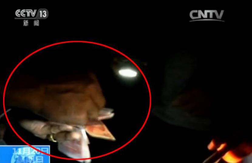 A screenshot from the CCTV report shows a smuggler paying cash to secure safe passage for his truck and its cargo across the China-Vietnam border.