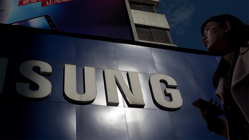 A pedestrian holding a mobile phone walks past a Samsung sign outside of a store in Guangzhou, Guangdong province, Nov. 30, 2013. Bloomberg/Getty Images/VCG