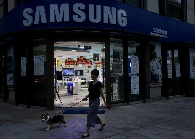 A woman walking a dog passes by a Samsung store in Shanghai, Oct. 11, 2016. Jia Ru/Sixth Tone