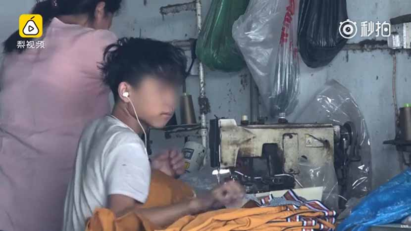 A screenshot from a video news report shows a young boy working at a clothing workshop.