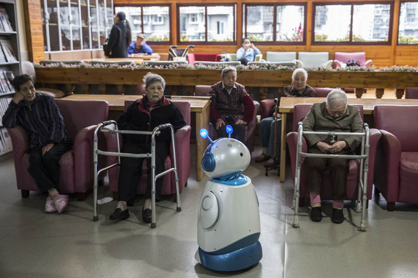 The robot Ah Tie 'stands' in front of a group of elderly people at the Hangzhou Social Welfare Center, Zhejiang province, Oct. 28, 2016. Chen Ronghui/Sixth Tone