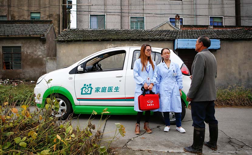Two family doctors talk with a local resident in front of an electric car that is specially used to take doctors to villages, Jinshan District, Shanghai, Oct. 31, 2016. IC