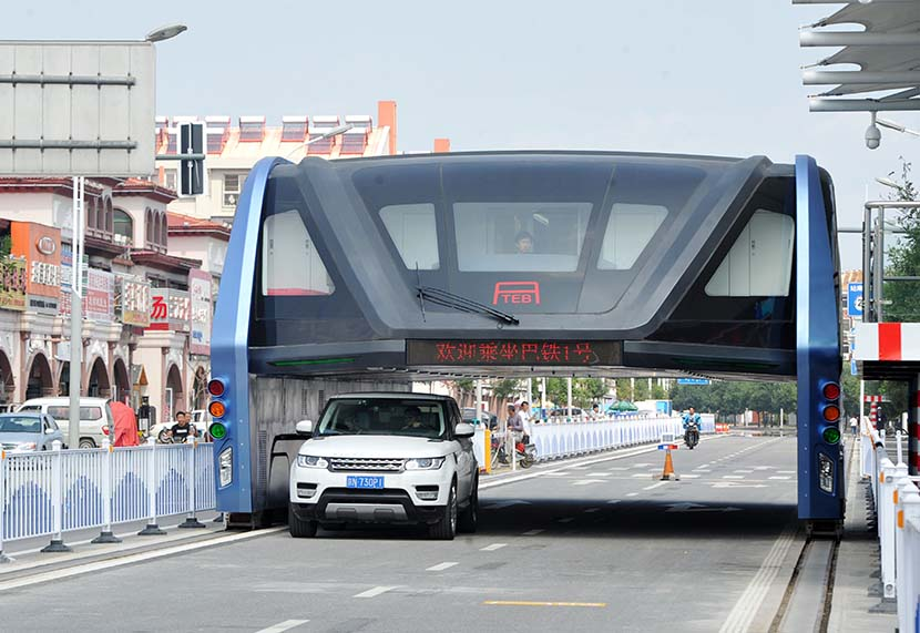 An SUV drives underneath the 'Transit Elevated Bus' in Qinhuangdao, Hebei province, Sept. 5, 2016. VCG