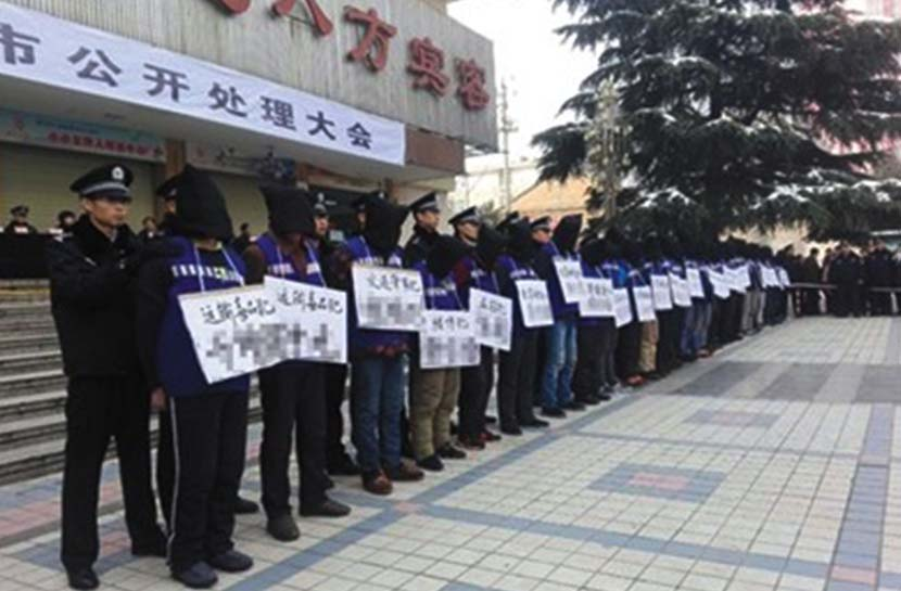 Criminal suspects wear signs displaying their names and charges during the public sentencing in Xingping, Shaanxi province, Nov. 25, 2016. @Zhoupengan from Weibo