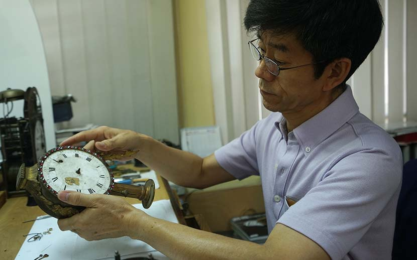 Wang Jin repairs a clock in his studio at the Forbidden City, Beijing, July 28, 2016. Courtesy of the documentary's crew