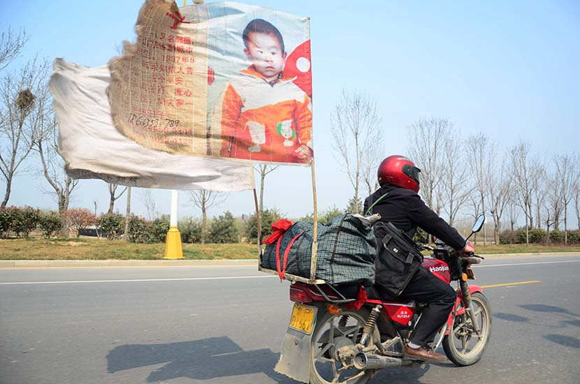 A father from Liaocheng, Shandong province, rides a motorcycle with a flag featuring his missing son's portrait, March 25, 2015. He has visited most of China's provinces by motorcycle in search of his son. Wei Peng/VCG