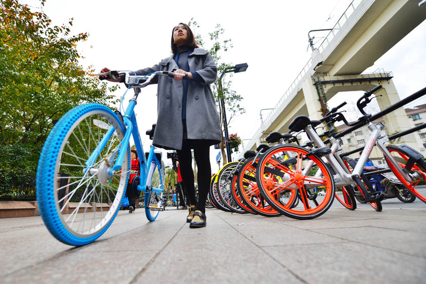 A woman with a Xiaoming bike passes by a line of Ofo and Mobike rentable bicycles in Shanghai, Nov. 29, 2016. Shen Chunchen/VCG