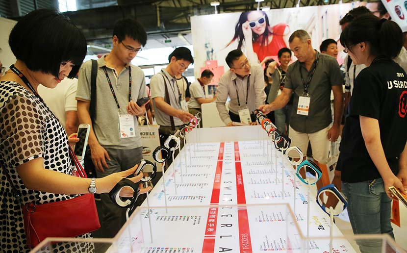 People try out wristwatch-like fitness trackers during a wearable-device exhibition in Shanghai, July 15, 2015. Pei Xin/Xinhua