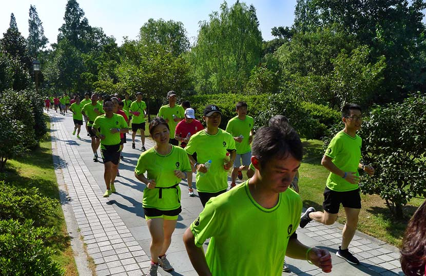 Runners take part in an event organized by Codoon at Xixi National Wetland Park, Hangzhou, Zhejiang province, Aug. 1, 2015. Wang Chuan/IC