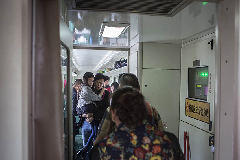Chen Chunchun's partner Lei Yu carries her on a train in Jiashan, Zhejiang province, May 25, 2016. Zhang Lijie for Sixth Tone