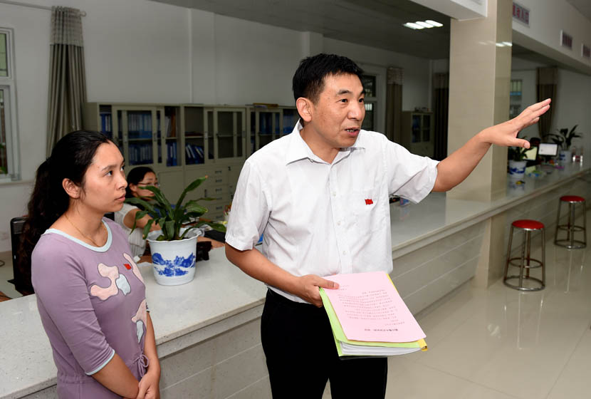 Wu Aiguo gestures during a tour of a community center in Guangde County, Anhui province, June 26, 2015. Liu Junxi/Xinhua