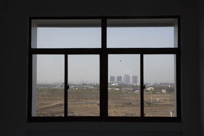 The former site of the Changlong Chemicals Company is seen through the window of a Changzhou Foreign Languages School building, Changzhou, Jiangsu province, April 19, 2016. Zhou Pinglang/Sixth Tone