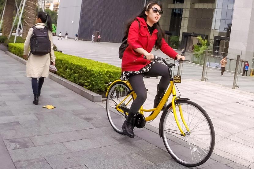 A woman rides an Ofo bike in Shenzhen, Guangdong province, Nov. 25, 2016. Liang Xiashun/VCG