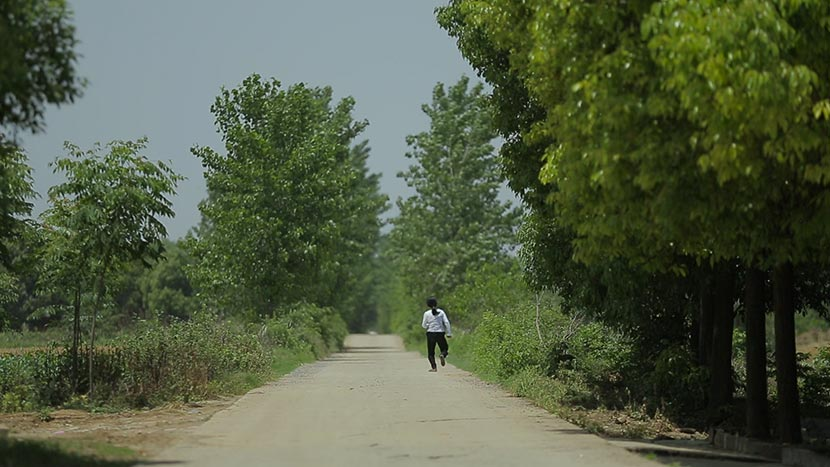 A still frame from 'Still Tomorrow' shows Yu Xiuhua walking along a country road. Courtesy of Fan Jian